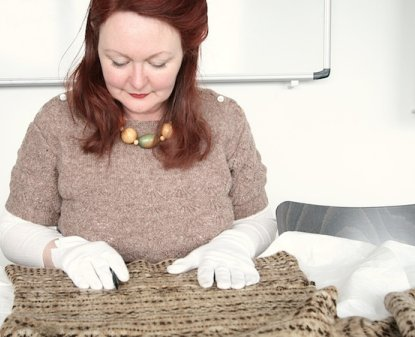 Vintage Shetland Project - Susan Crawford examines a garment at the Shetland Museum